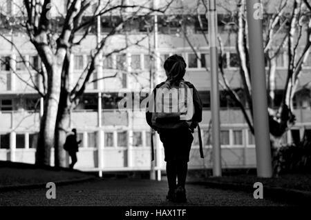 Kleines Mädchen (6 Jahre) mit Schultasche geht zur Schule allein durch sich selbst auf der Straße. Bildungskonzept. - Stockfoto
