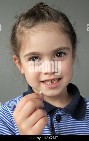Fröhliches junges Mädchen (6 Jahre) hält ihre ersten Milchzähne fallen, in die Kamera schaut. Kindheit im Gesundheitswesen Konzept. echte Menschen kopieren Raum