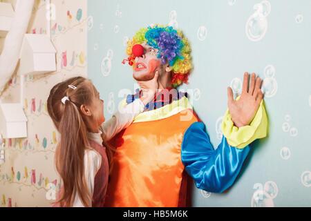 Grausame Mädchen spielen mit Angst clown - Stockfoto