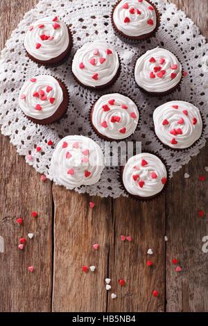 Frisch red Velvet Cupcakes mit einer Großaufnahme lacy Serviette auf dem Tisch. vertikale Ansicht von oben - Stockfoto