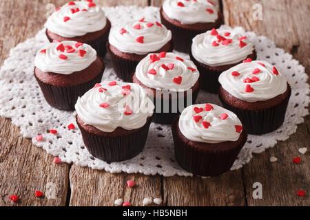 Tastyred Velvet Cupcakes mit einer Großaufnahme lacy Serviette auf dem Tisch. Horizontale - Stockfoto