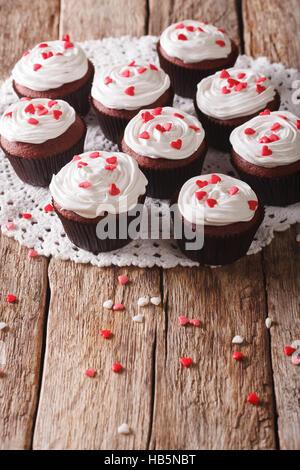 Frisch red Velvet Cupcakes mit einer Großaufnahme lacy Serviette auf dem Tisch. Vertikal - Stockfoto