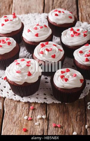 leckere rote samt-kleine Kuchen mit einer Großaufnahme lacy Serviette auf dem Tisch. Vertikal - Stockfoto