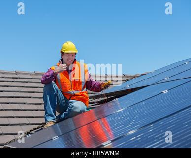 Arbeiter und Sonnenkollektoren - Stockfoto