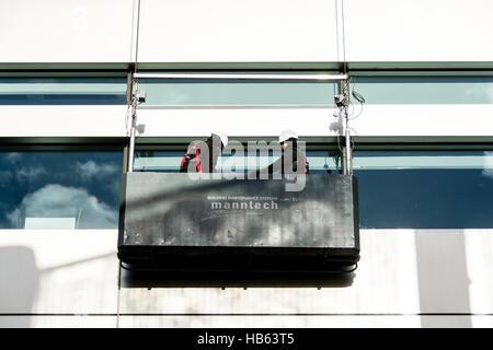 Fensterputzer in einer Gondel außerhalb der Hauptsitz von UBS an Broadgate Kreis, Broadgate, City of London, England, - Stockfoto