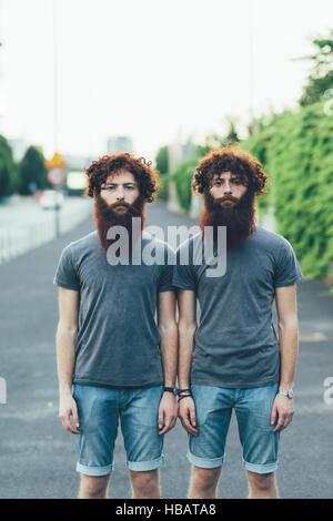 Porträt von identischen Erwachsene männliche Zwillinge mit roten Haaren und Bärten auf Bürgersteig - Stockfoto