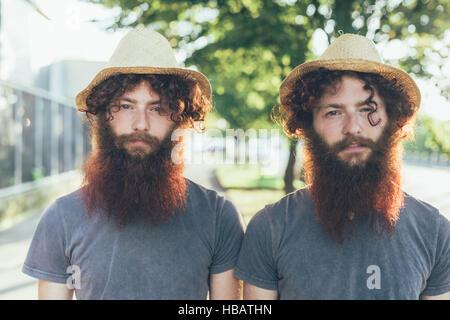Porträt von identischen männliche Hipster Zwillinge tragen Strohhüte auf Bürgersteig - Stockfoto