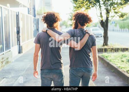 Rückansicht des identisch männliche Erwachsene Zwillinge am Bürgersteig spazieren - Stockfoto