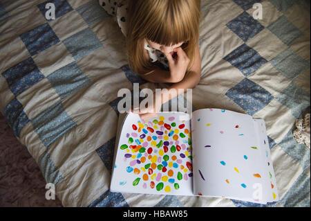 Junges Mädchen auf Bett Buch - Stockfoto