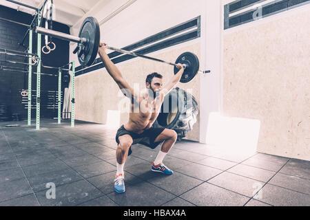Junger Mann Gewichtheben Langhantel in cross-Training-Fitness-Studio - Stockfoto