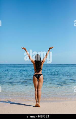 Rückansicht des jungen Frau mit Bikini am Strand. Junge Frau im Badeanzug stehen an der Küste mit ihren Händen in - Stockfoto