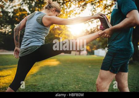 Männlicher Coach hilft jungen Frau im Park trainieren. Trainer helfen Frau Bein Training dehnen. - Stockfoto