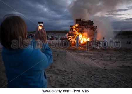 Eine Frau benutzt ihr Handy ein Foto von einem riesigen Anleihe Feuer auf Nauset Strand nehmen. - Stockfoto
