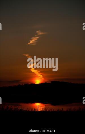 Schöne Linie der Wolken auf einem Sommer Sonnenuntergang Hintergrund spiegelt sich im Teich. Stockfoto