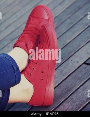 Rote Turnschuhe auf Holzuntergrund - Stockfoto