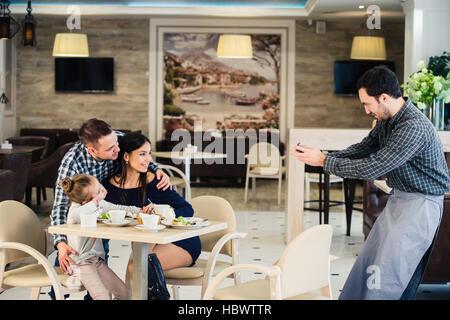 Familie, Elternschaft, Technologie, Menschen Konzept - glückliche Mutter, Vater und kleine Mädchen beim Abendessen - Stockfoto