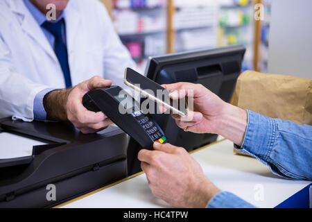 Kunde die Zahlung durch Smartphone in Zahlung terminal - Stockfoto