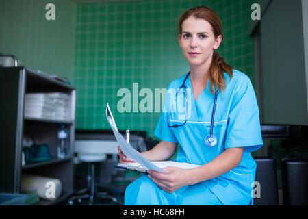 Porträt von Krankenschwester hält Krankenbericht - Stockfoto