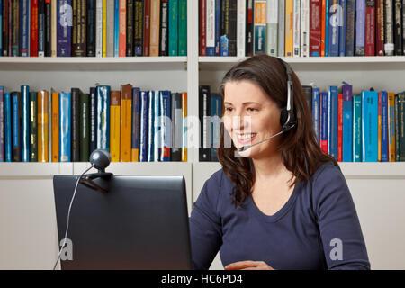 Frau mittleren Alters mit Computer, Headset und Webcam mit Freunden zu reden über viewphone - Stockfoto