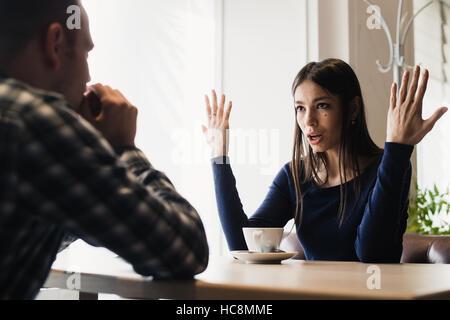 Junges Paar in einem Café streiten. Probleme in Beziehungen. - Stockfoto
