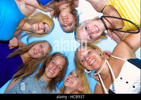 Symbolisches Bild für Freundeskreis, Kopf an Kopf im Kreis stehen Mädchen im Teenageralter - Stockfoto