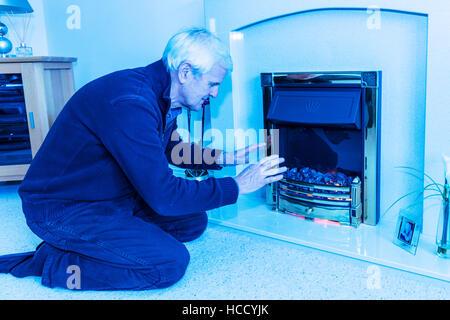 OAP versucht, warme wärmende Hände in der Nähe von Feuer zu halten halten Rechnungen nach unten nicht leisten hohe - Stockfoto