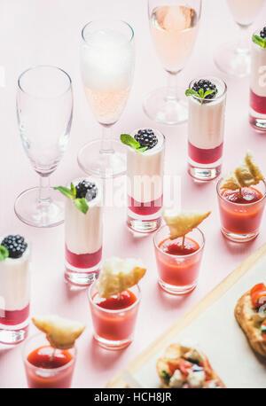Nahaufnahme von verschiedenen Snacks, Brushettas, Gazpacho Aufnahmen, Desserts mit Beeren und Champagner auf Firmenfeier, - Stockfoto