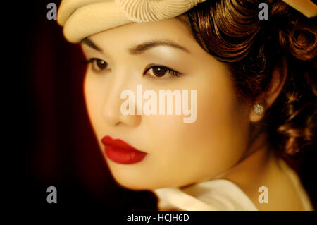 Eine asiatische Frau in ihren frühen zwanziger Jahren, gekleidet in der Kleidung der frühen vierziger Jahre, blickt - Stockfoto