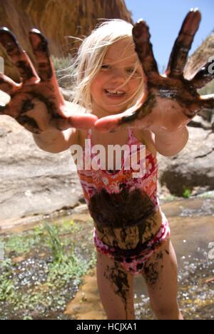 Blonde Mädchen Badeanzug spielt in einem Fluss in der Wüste mit Händen im Schlamm bedeckt. - Stockfoto