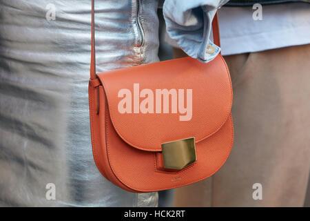 Frau mit Celine orange Tasche und Silber Rock vor Salvatore Ferragamo Modenschau, Milan Fashion Week Streetstyle - Stockfoto
