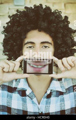 Junge lächelnd über ein Mobiltelefon