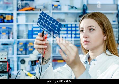 -MODELL VERÖFFENTLICHT. Mädchen-Solarzellen halten. - Stockfoto