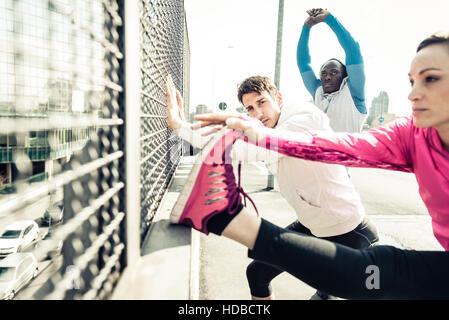 Drei multiethnischen sportliche Läufer dehnen und ruhen während einer Trainingseinheit in einem städtischen Gebiet - Stockfoto