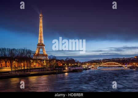 Der Eiffelturm in der Dämmerung mit den Banken des Flusses Seine und die Passerelle Debilly beleuchtet. Paris, Frankreich - Stockfoto