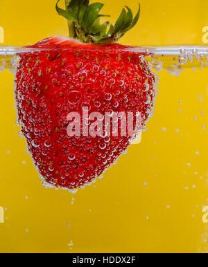 Erdbeere im Mineralwasser vor einem gelben Hintergrund - Stockfoto
