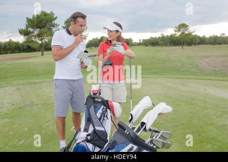 Paar am Golfplatz hält Broschüre - Stockfoto