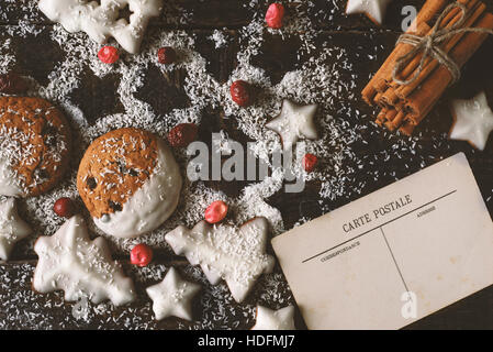 Weihnachtsplätzchen mit Postkarte und Zimt auf den hölzernen Hintergrund