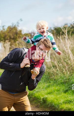 Ein Mann und ein kleiner Junge auf einem Spaziergang, ein Vater mit seinem Sohn eine Huckepack. - Stockfoto