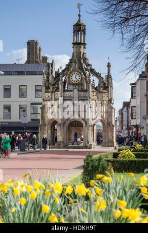 Weststraße, eine Fußgängerzone und Chichester Market Cross mit Feder Narzissen. Chichester, West Sussex, UK - Stockfoto