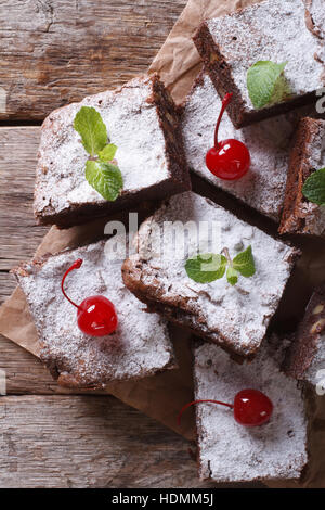 Brownie-Kuchen mit Minze und Kirsche auf dem Papier. vertikale Ansicht von oben, rustikalen Stil - Stockfoto