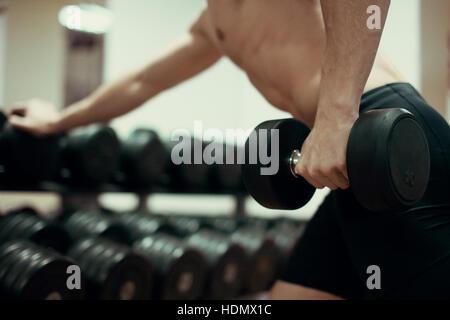 Nahaufnahme eines muskulösen jungen Mannes im Fitnessstudio Gewichte zu heben. - Stockfoto