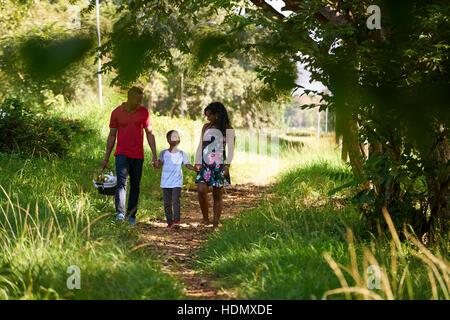 Brautpaar schwarz mit Sohn im Stadtpark spazieren. Afroamerikanische Familie mit junger Mann, Frau und Kind tun - Stockfoto
