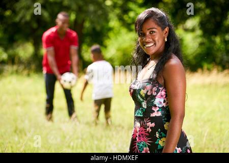 Glückliche schwarze Menschen im Park. Afroamerikanische Familie mit junger Vater und Sohn Spaß mit Fußball. Porträt - Stockfoto