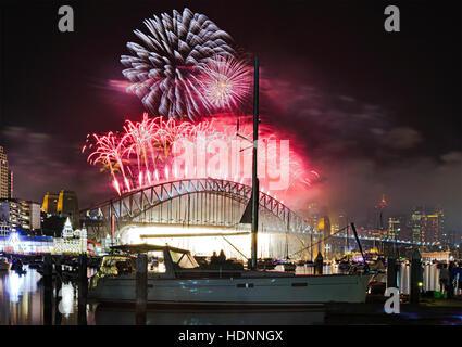 Silvester-Feuerwerk in Sydney über Hafen, Brücke und Stadt Wahrzeichen. Riesige Feuerbälle Herunterfallen zu Firefall - Stockfoto