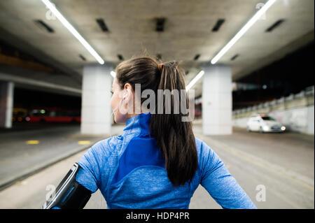 Junge Läufer unter der Brücke am Abend, ruhen - Stockfoto