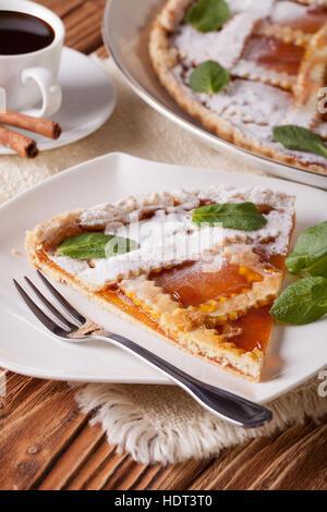Stück des italienischen Torte mit Marillenmarmelade und Kaffee auf dem Tisch. Vertikal - Stockfoto