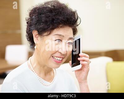 Senior Asiatin auf Couch telefonieren mit Handy - Stockfoto