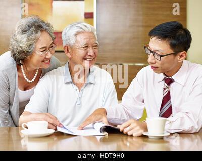 hochrangige asiatische paar hören einen Verkauf Vertreter, glücklich und lächelnd - Stockfoto