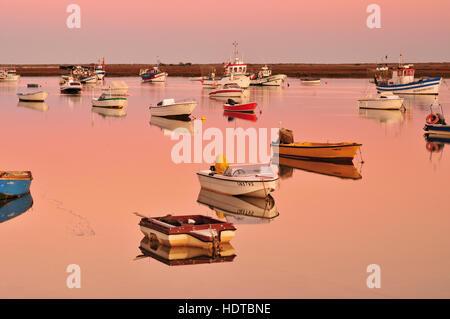 Fischerboote ankern in den ruhigen Gewässern des Ria Formosa Lagune in der Dämmerung - Stockfoto