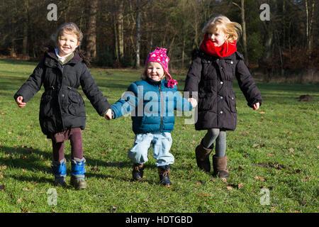 Drei Schwestern: Mädchen Alter 4, 2 & 6 Jahre, vier, zwei und sechs Jahre alt, laufen laufen spielen im Rasen Park - Stockfoto